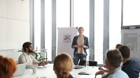 Smiling businesswoman giving presentation to colleagues