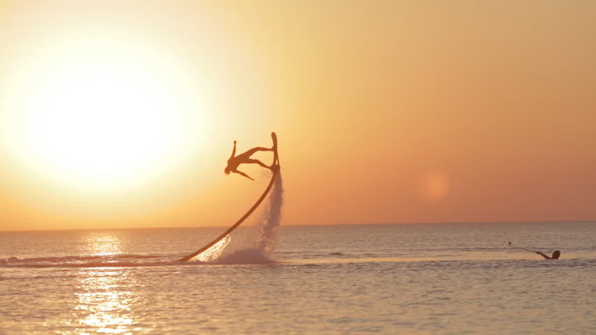 Silhouette of a Man Having Fun on Flyboard in the Sea at Sunset