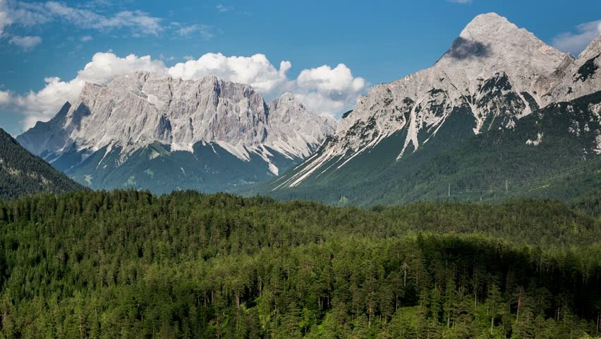 Zugspitze mountains with flowing clouds over the forest. Blindsee. Timelapse HD