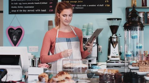 Female in cake shop checking inventory on digital tablet