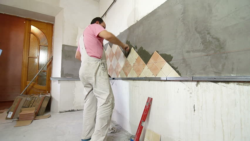 Man Applying Ceramic Tile To A Kitchen Wall, Working With Trowel, Wide  Angle