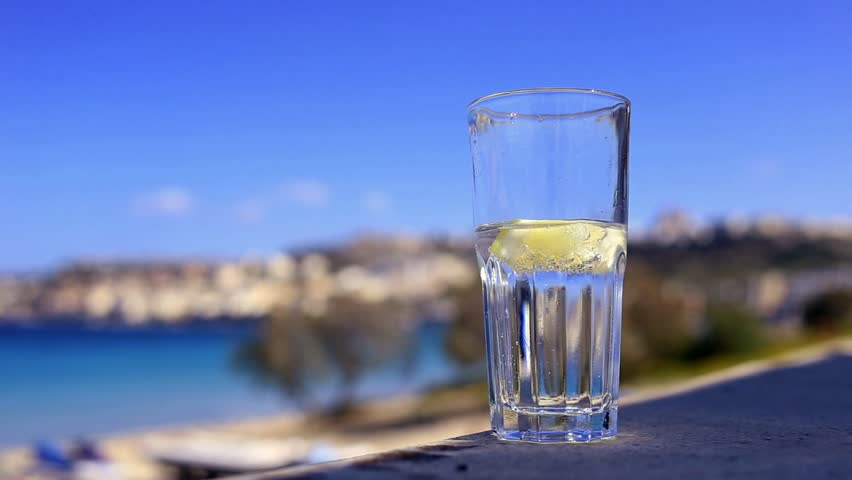 Pouring sparkling water into glass with lemon and ice on the beach at summertime - Mellieha bay, Malta