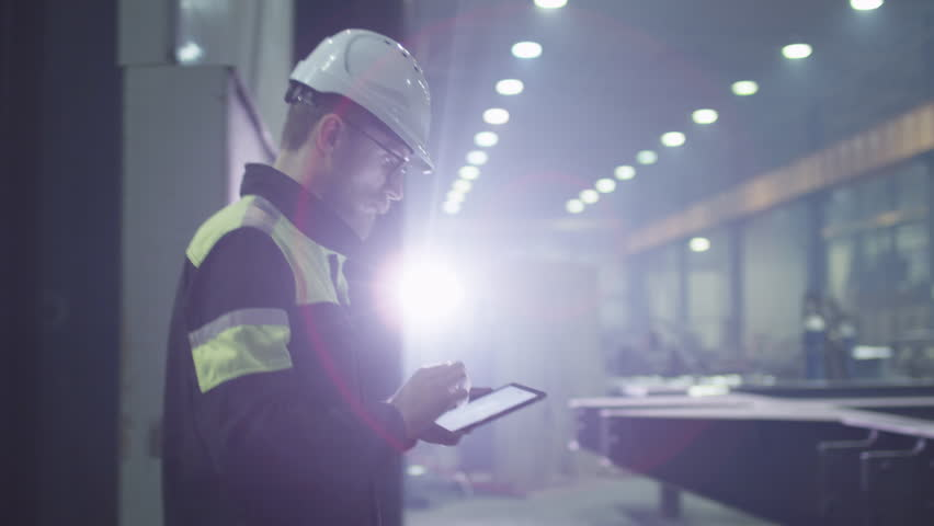 Engineer in hardhat is moving through a heavy industry factory with a tablet computer. Is greeting a worker with a handshake. Shot on RED Cinema Camera. | Shutterstock Video #15514921
