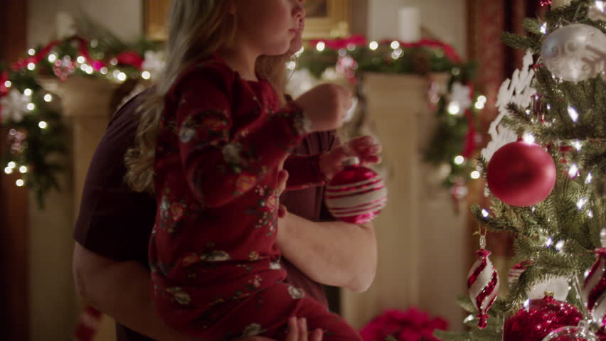 Medium panning shot of father and daughter decorating Christmas tree / Cedar Hills, Utah, United States