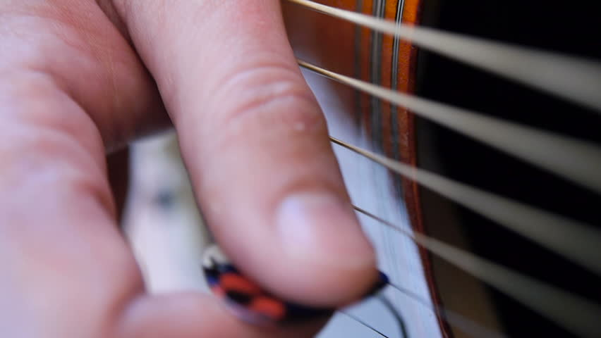 Man playing accoustic guitar outdoors, close up footage