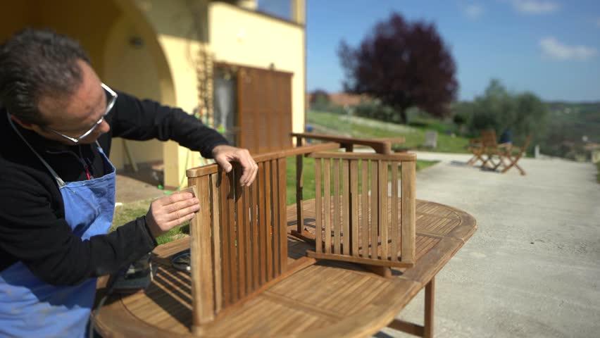 Handsome carpenter restoring a wooden chair with sandpaper. Garden furniture.