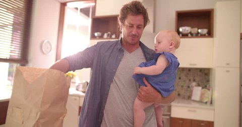 Modern dad standing and holding infant daughter while unpacking groceries from paper back on counter, in sunlight filled kitchen.