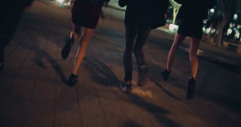 Back view of the legs of some happy friends in running in city and enjoying night life.