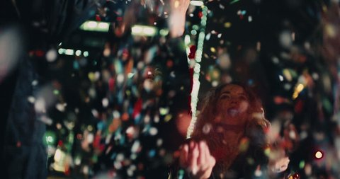 Teenager hipster friends celebrating a night party by blowing colourfull confetti with city lights in the background