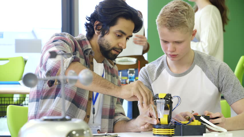 Young, male teacher helping his students build a robotic arm. | Shutterstock HD Video #15582943