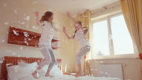Happy daughter and mother jumping and spinning on the bed. Among the fluff and feathers. Slowmotion. SonyA6300