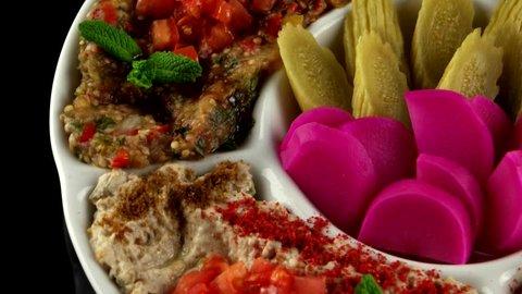 Plate of assorted appetizer (Hummus, Baba Ganouj, Mutabal, Dolma vegetable, Syrian pickled cucumbers, Pickled turnips), loop