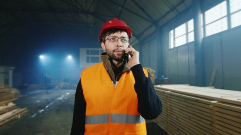 : Builder in a helmet and a bright vest goes on a warehouse of building materials, talking on the phone. Warehouse work and logistics concept