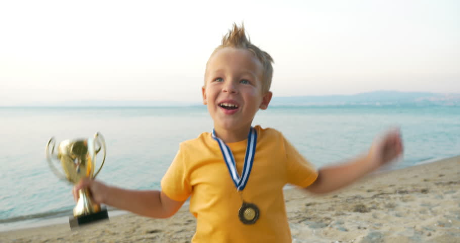 Little child with cup and medal jumping for joy to be the winner. He shouting and kissing prize at the seaside