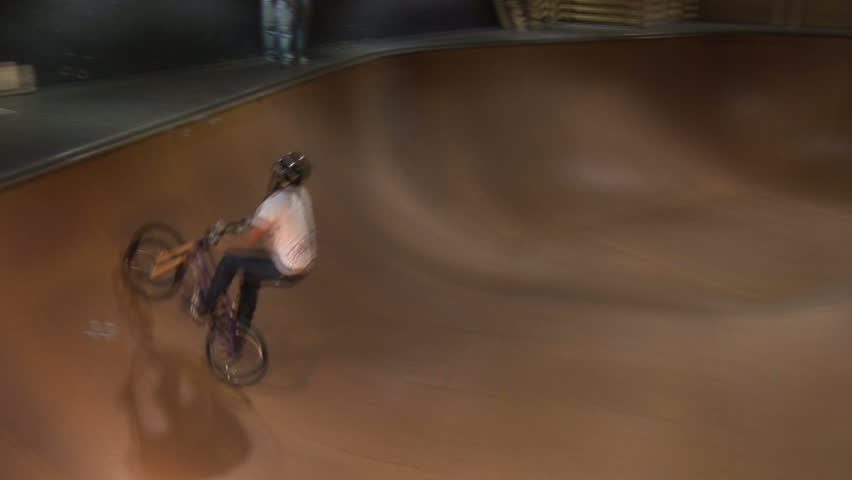BMX rider performs tricks in bowl