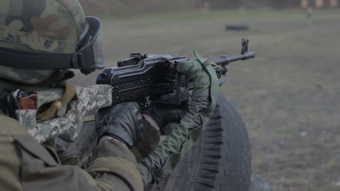 A soldier with a machine gun on a military firing range shooting at a target.