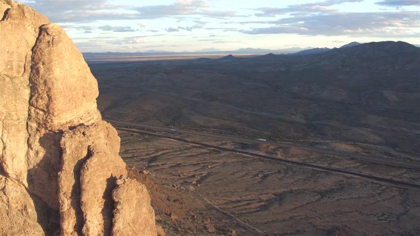 AERIAL: Truck speeding down the highway through big rocky desert valley in the West