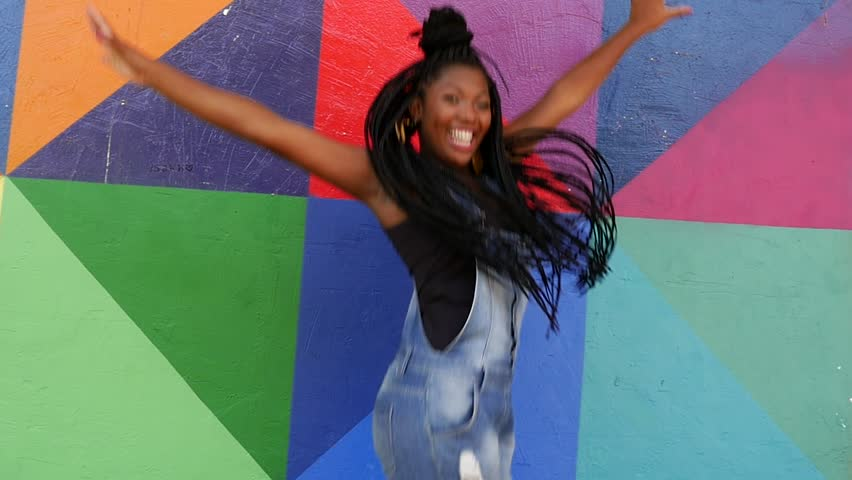 Young Afro Brazilian woman jumping on colorful background