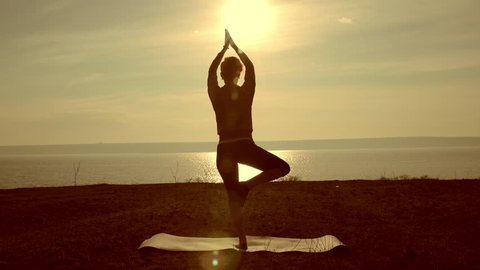 Young woman silhouette practicing yoga on the sea beach at sunset. Slim woman doing gymnastics over morning sun. Girl with a slender figure practices yoga near the ocean at sunrise. Sport and health.