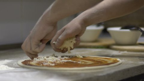 Chef putting cheese topping on his pizza base. Slow motion