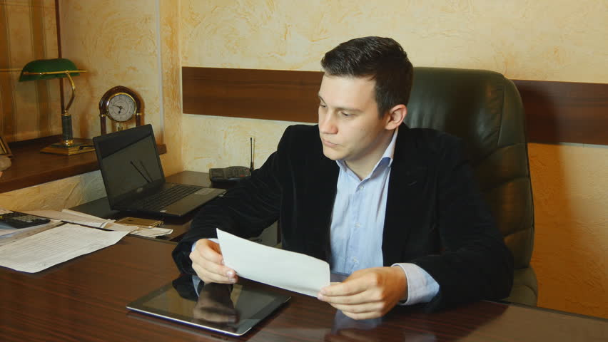 Serious young businessman looking report in office. Businessman in casual working at desk and analyze the document .Businessman working with documents in the office. | Shutterstock HD Video #15753673