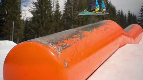 snowboard slow motion,snowboarder jumping on kink rail slow motion close up