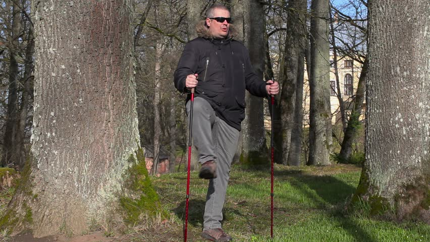 Hiker with walking sticks warm up in the park | Shutterstock HD Video #15777403