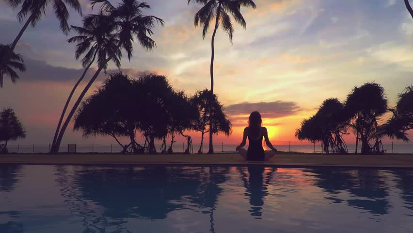 Woman training yoga at sunset near the swimming pool. wide angle | Shutterstock HD Video #15787723