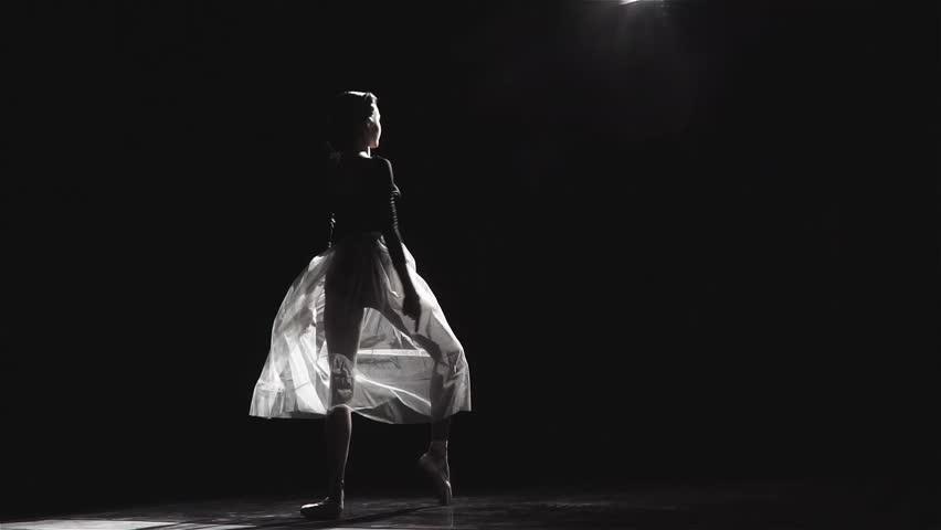 Slow motion shot of a beautiful female ballet dancer on a black background