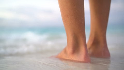 Close up of woman feet on beach. Girl getting her toes wet on vacation. Calm serene relaxing scene on with water splashing on feet in ocean on beautiful beach.