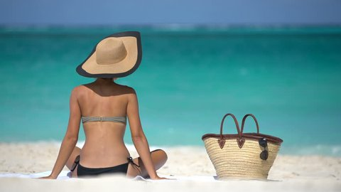 Woman on beach vacation putting on sunglasses enjoying summer vacation at beautiful tropical resort island. Pretty lady sitting on beach towel wearing classic straw sun hat and stylish beach bag.