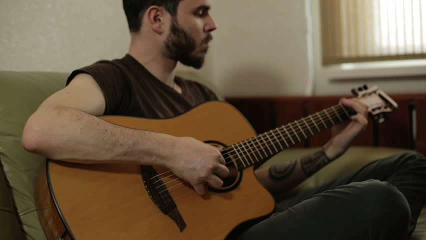 A man with a beard playing the guitar. An attractive man with a black beard and mustache playing the acoustic guitar. He is sitting cross-legged on an olive sofa near window. Camera goes up and down. #15797683