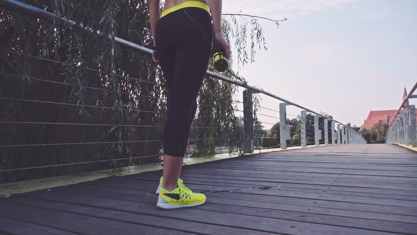 Runner woman feet running in the city exercising outdoors. Steadicam stabilized shot 4K. Sportswoman wearing barefoot sports shoes while training on the sunny city bridge. Lens Flare.