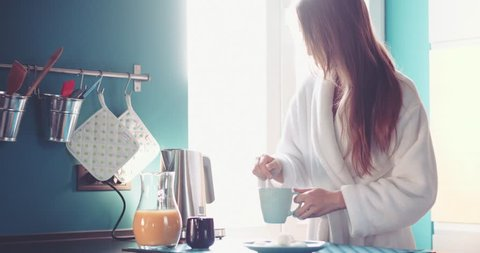 Woman enjoying the morning, Slow Motion 4K DCi. Young beautiful relaxed woman pouring cream into a cup of coffee by the window during calm morning in her cozy kitchen. Lazy morning at home concept.