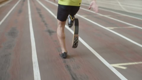 Follow shot of Paralympic amputee athlete with prosthetic leg running on track in slow motion, rear view, tilt up