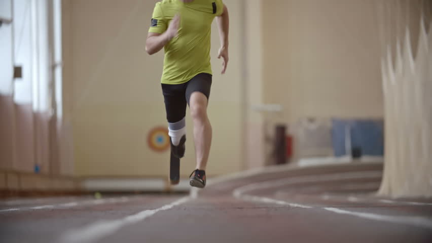 Paralympic athlete with prosthetic leg running on track towards the camera in slow motion