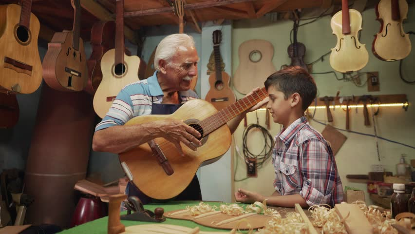 Old and young people showing love for music. Boy and senior man, happy kid and elderly person, grandfather teaching grandson how to play guitar and musical instrument in shop. Generation gap