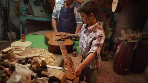 Old and young people showing love for music. Boy and senior man, happy kid and elderly person, grandpa showing guitars and instruments to grandchild in lutist workshop. Proud retired worker