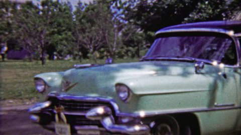 TOPEKA, KANSAS 1959: Teal Cadillac 4 door classic car parked in outdoor green space.