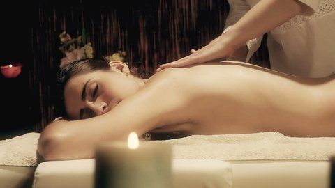 Dolly shot of beautiful young woman getting back massage in spa