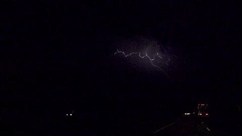 SLOW MOTION: Thunderstorm lightning bolt striking over the cars and trucks on a busy highway at night