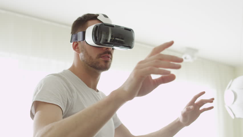 Man Wearing VR Headset at Living Room. Using Gestures with Hands. Shot on RED Cinema Camera.