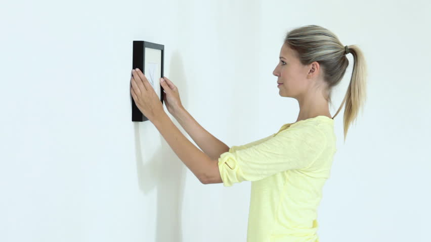July 15, 2010: Young woman hammering nail into wall and hanging picture