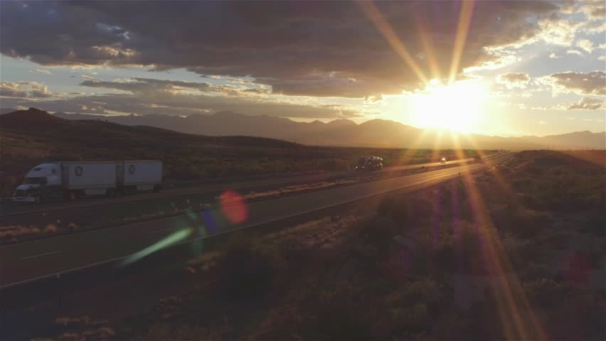 4K AERIAL: Cars and freight semi truck driving on busy highway across the country in beautiful summer evening. People on road trip traveling on busy freeway at golden sunset   Shutterstock HD Video #15953443
