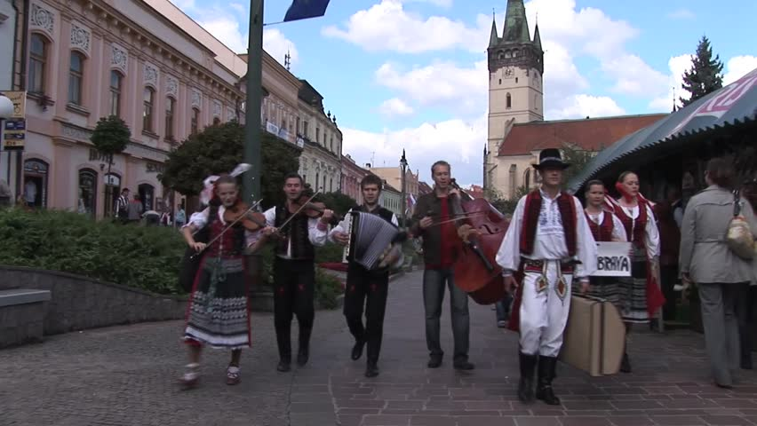 PRESOV, SLOVAKIA - SEPTEMBER 10, 2007: Street musicians walk towards camera carrying double bass, accordion