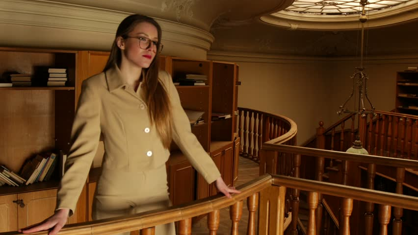 On a warm pale light in the old library beautiful young woman in suit and  glasses choose a book to read cebdad6c1