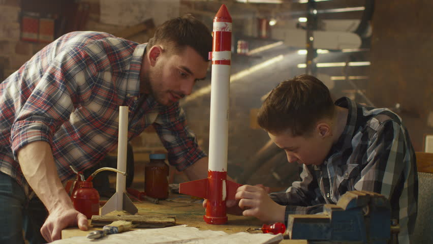 Father and son are modeling a toy rocket in a garage at home. Shot on RED Cinema Camera in 4K (UHD).