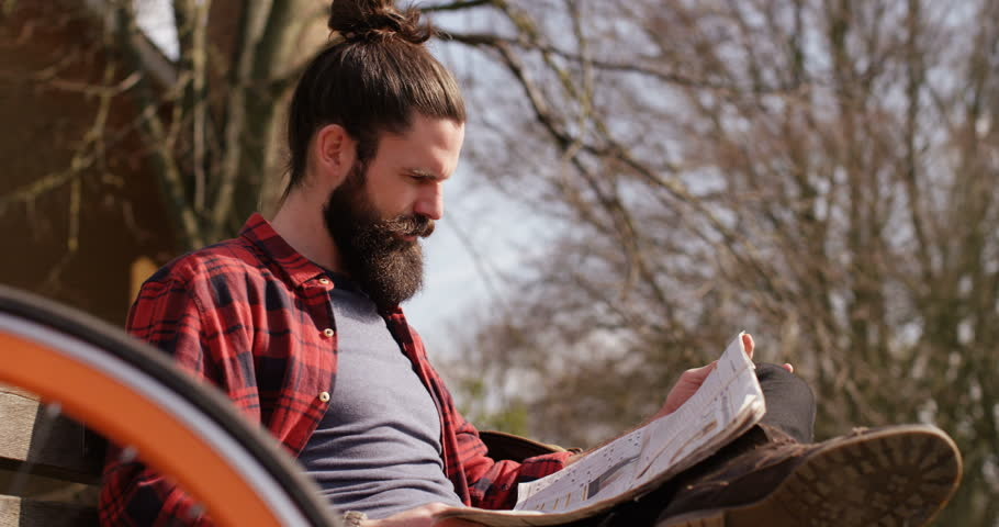 4k, A young man reading a newspaper in a park as he takes a break from cycling. | Shutterstock HD Video #16003693