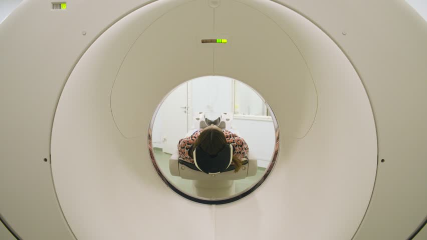 Unrecognizable woman with dark hair moving while lying inside mri