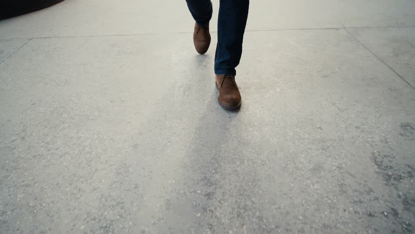 Walking on concrete : close-up view of man's leather shoes